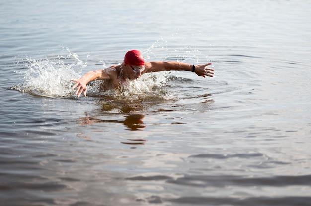 Молодой человек с красной шапочкой плавает в озере