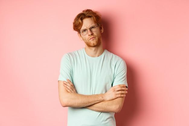 赤い髪とあごひげを生やし、眼鏡とtシャツを着て、胸に腕を組んで、懐疑的で疑わしい表情を見つめながら眉をひそめ、ピンクの背景の上に立っている若い男。