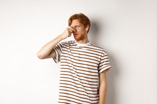 カメラを見つめ、悪臭から鼻を閉じた赤い髪の若い男は、何か臭い、白い背景のようにうんざりしているように見えます。