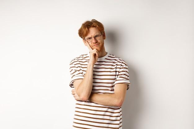 赤い乱雑な髪と眼鏡の若い男は、疑わしい顔をして、カメラを考えて目を細め、白い背景の上に思慮深く立っています。