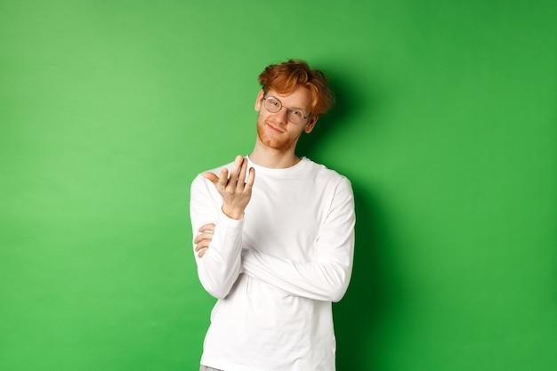 빨간색 지저분한 머리와 안경 젊은 남자, 기쁘게 웃 고 녹색 배경 위에 서있는 카메라, 차례 제스처에 손을 가리키는.