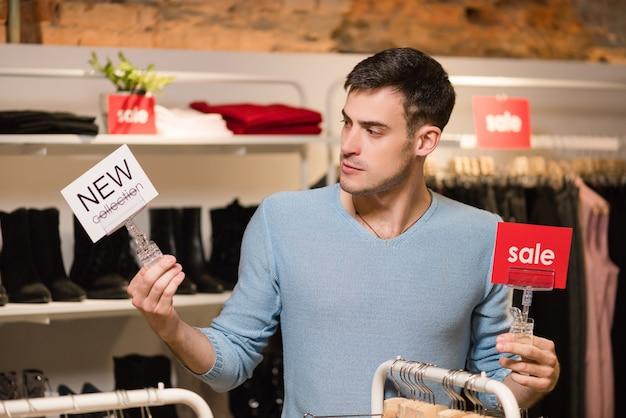 Молодой человек с красной распродажей и белым знаком новой коллекции
