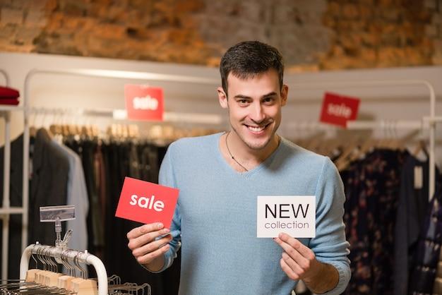 Молодой человек с красной распродажей и белыми бирками новой коллекции