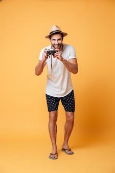 Молодой человек с ретро камерой делает фото