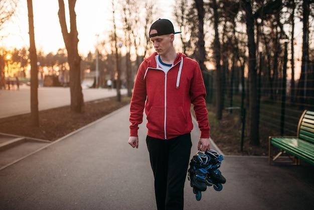 ローラースケートを手に都市公園を歩いている若い男。男性ローラースケートレジャー