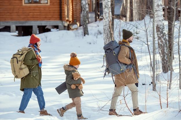 Молодой человек с рюкзаком, его жена и их милая маленькая дочь с игрушечным медведем движутся к загородному дому в лесу в зимний день