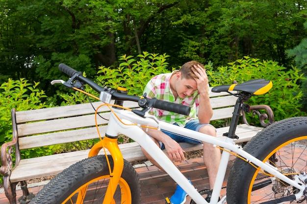 아름다운 녹색 공원의 벽돌 보도에 뚱뚱한 타이어가 주차된 자전거 근처 벤치에 앉아 슬픈 표정을 한 청년