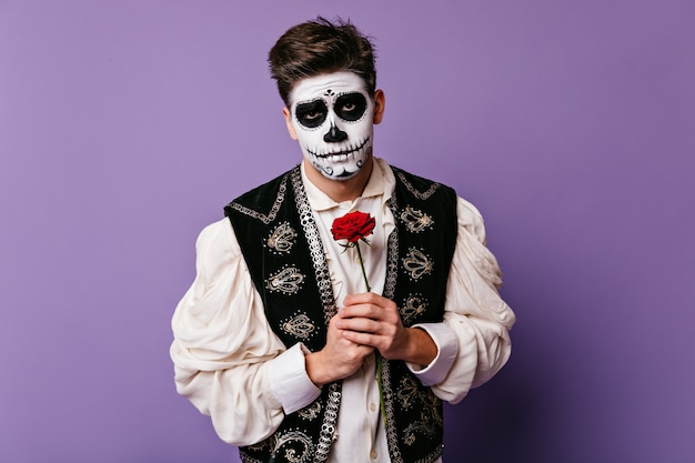 Young man with sad look tenderly holds red flower at his chest. closeup portrait of brunet in halloween outfit.