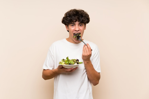 Young man with salad over isolated green wall