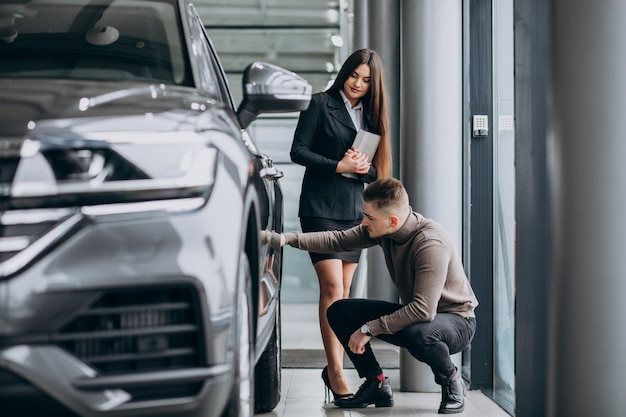 Young man with saleswoman at a car showroom