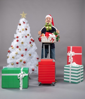 Young man with santa hat holding gift basket with both hands near xmas tree on grey
