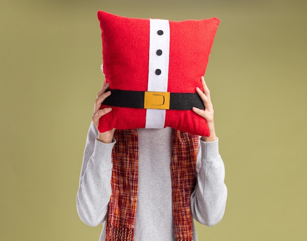 Young man with   scarf around hiding his face behind christmas pillow standing over green wall
