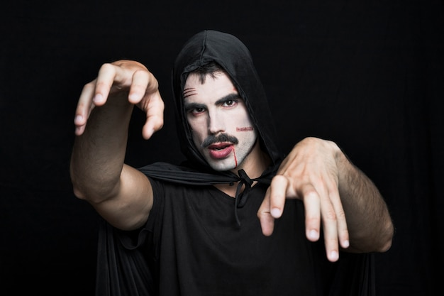 Young man with scars on pale face in halloween costume posing in studio