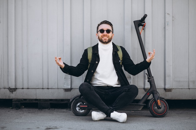 Young man with scooter, sitting on the ground