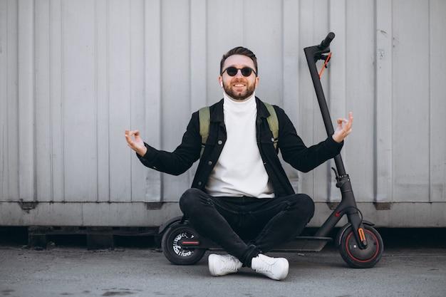 Молодой человек с скутер, сидя на земле