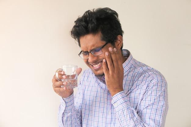 敏感な歯と冷たい水のガラスを持つ若い男。