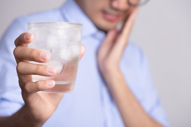Young man with sensitive teeth and hand holding glass of cold water with ice