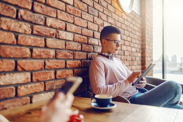 Молодой человек с серьезным выражением лица и одетый элегантный случайный с помощью планшета