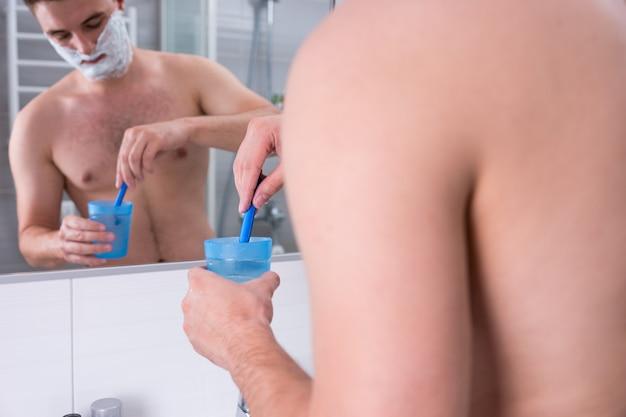뺨에 면도 거품이 있는 젊은 남자는 현대적인 타일 욕실에서 거울 앞에 서 있는 물로 컵에 면도기를 씻습니다