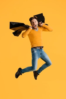 Young man with shopping bags jumping