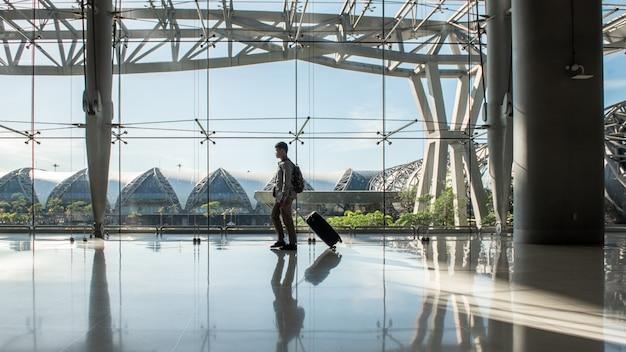 Молодой человек с сумкой и ручной клади гуляет в аэропорту суварнабхуми, таиланд