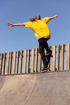 Молодой человек со скейтбордом, прыжки в полный рост