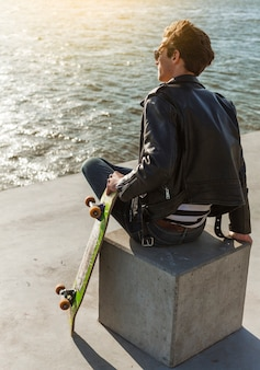 Young man with a skateboard near the sea