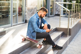 Young man with skateboard using mobile phone