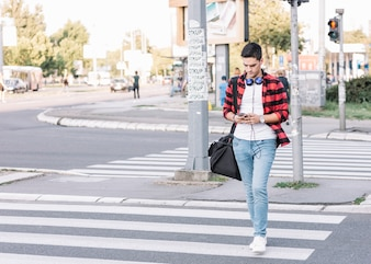 Young man with smartphone crossing street