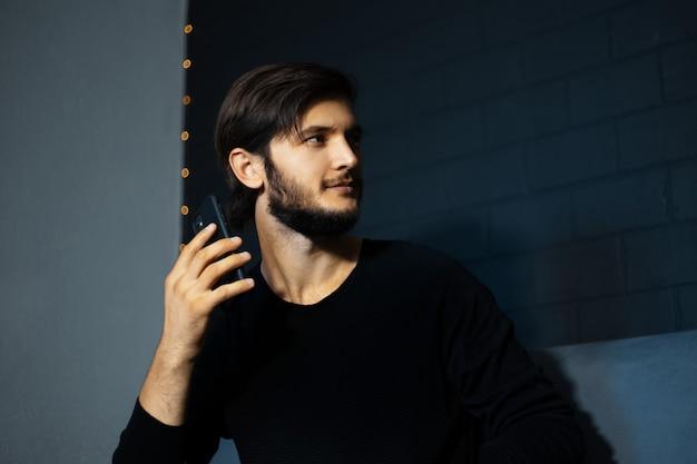スマートフォンを手に、黒いレンガの壁を背景にソファに座っている若い男。