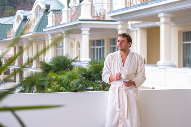 A young man with a smile on his face in a white bathrobe is standing on the open veranda of the park hotel with a cup of morning tea or coffee.