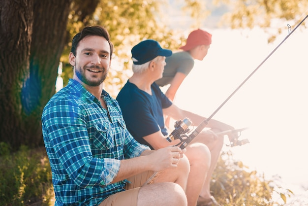 Young man with son and father fishing on river.