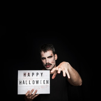 Young man with spooky makeup and signboard