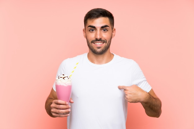 Young man with strawberry milkshake over isolated pink wall with surprise facial expression