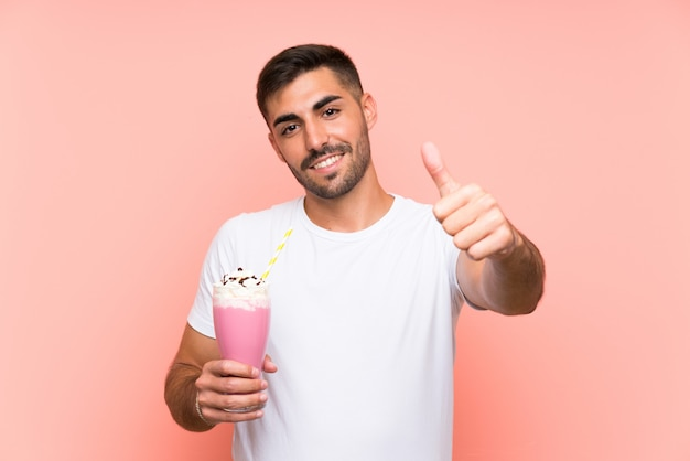 Young man with strawberry milkshake over isolated pink wall with thumbs up because something good