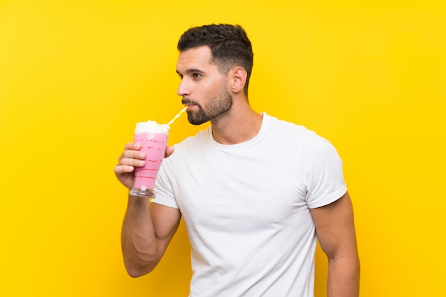 Young man with strawberry milkshake over isolated yellow wall