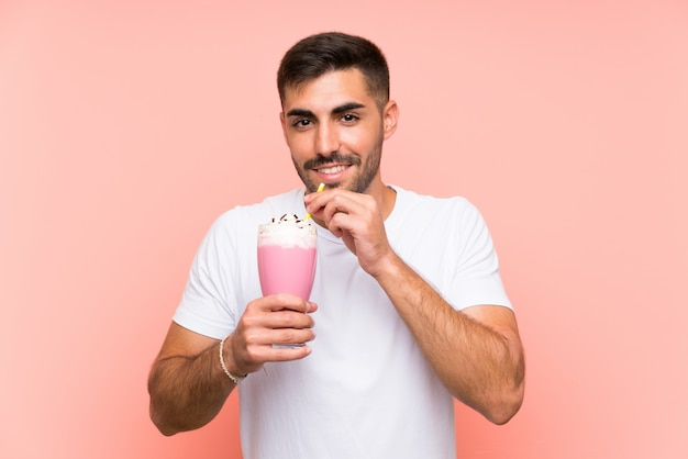 Young man with strawberry milkshake