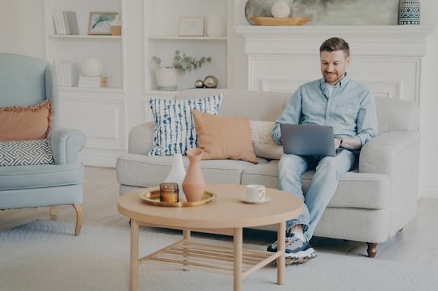 Young man with stubble working as freelancer, using notebook for work, trying to finish commission in time while sitting on comfy small beige couch in modern themed living room
