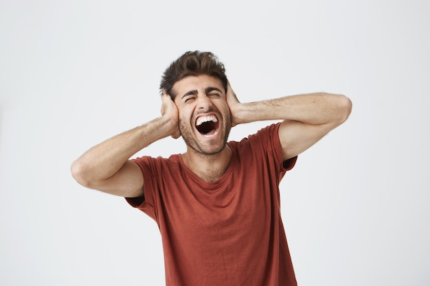Young man with stylish hair covering his ears and shouting. went into hysterics because of argument with his girlfriend or parents. do not want to continue listening, opened his mouth in shriek expres