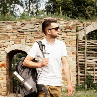 城の遺跡でサングラスをかけた若い男