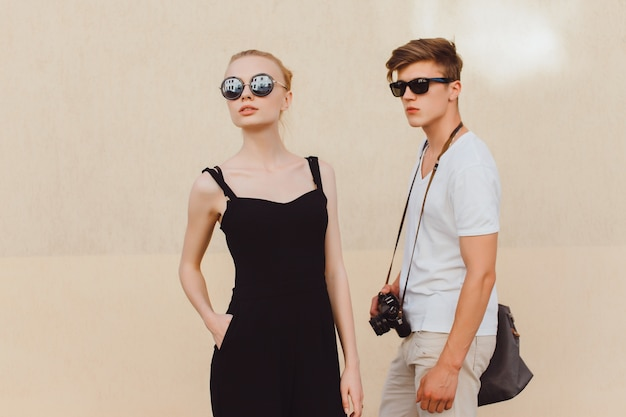 Young man with sunglasses and boy with a camera