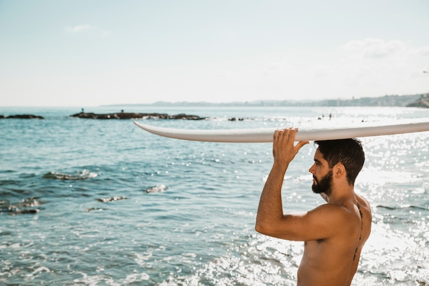Young man with surf board on head on shore near water