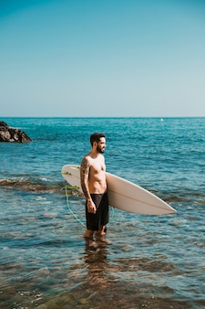Young man with surf board in water