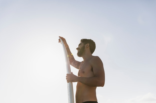 Young man with surfboard against clear sky