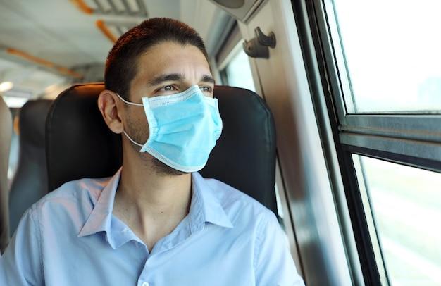 Молодой человек с хирургической маской, глядя через окно поезда