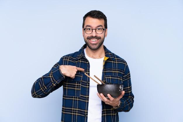 Молодой человек с удивленным выражением лица, держа миску лапши с палочками для еды