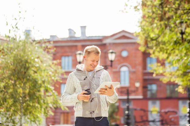 紙コップのコーヒーで秋の朝のニュースを読んでタブレットコンピューターを持つ若い男