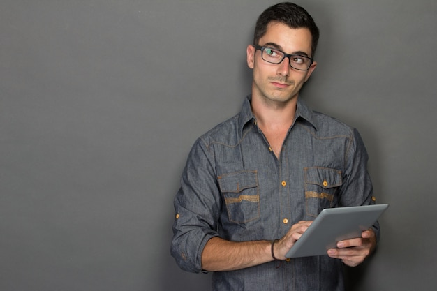 Young man with tablet looking up to copy space