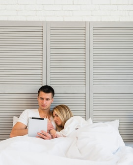 Young man withtablet near sleeping woman in bed