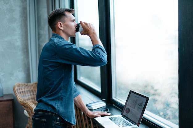 窓の近くに立っているテイクアウトコーヒーと若い男